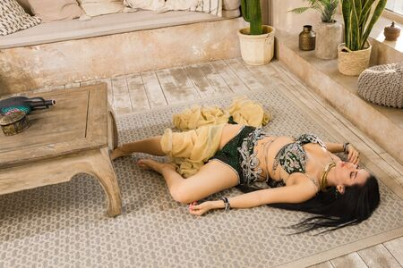 Photo for Crime scene imitation: lifeless woman in a traditional oriental costume lying on a floor - Royalty Free Image