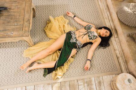 Photo pour Crime scene imitation: lifeless woman in a traditional oriental costume lying on a floor - image libre de droit