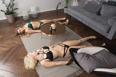 Photo for Crime scene imitation. Two lifeless beautiful women in a room. The were shot in the chest - Royalty Free Image