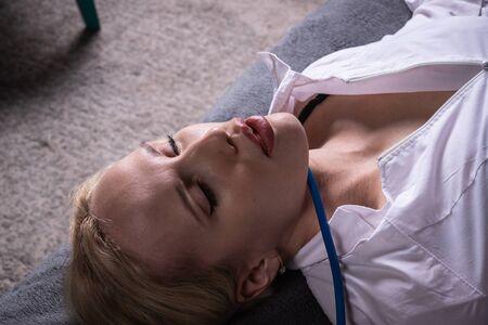Photo for Crime scene imitation. Strangled nurse in the bedroom - Royalty Free Image