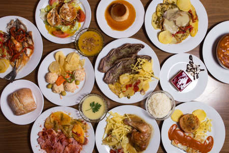 An overhead photo of many different Spanish tapas foods, shot from above on a dark rustic background