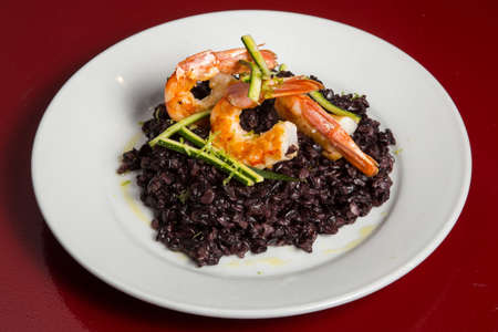 Foto de Arroz negro. Black rice. Typical spanish food in mediterranean zone made with rice, onion, tomato, squids and squid ink. Can be eated with ali oli sauce - Imagen libre de derechos