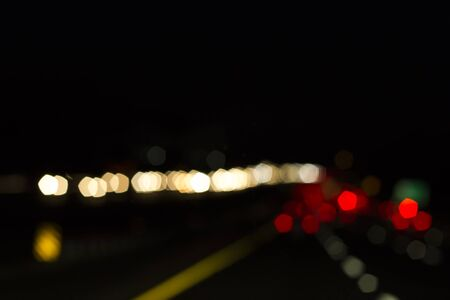 Traffic lights of the night city road. beautiful background of bokeh lights at night on road with car