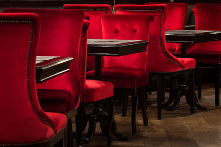 Red velvet chairs and tables on a wooden floor black, elegant piece of interior of restaurant