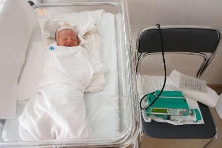 Newborn baby sleeping on a drip in a hospital