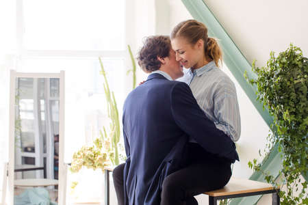 Photo pour Young man and woman in formal clothes about to have sex in office on table desk among green plants - image libre de droit