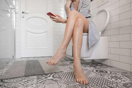 Foto de Woman sitting on the toilet with phone and surfing internet - Imagen libre de derechos