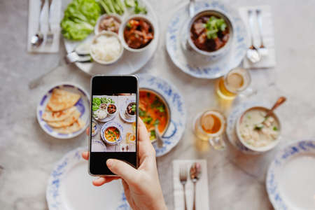 Foto de Hand of anonymous female using smartphone to take photos of delicious dishes on table - Imagen libre de derechos