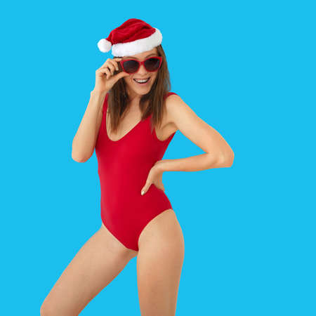 Photo for Positive slim female in red swimsuit and Christmas hat touching stylish sunglasses while standing against bright blue background - Royalty Free Image