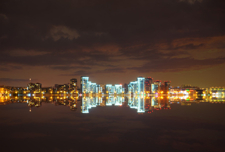 Brightly lit at night Kazan city center reflecting in the waters of Lake Kaban. Russia