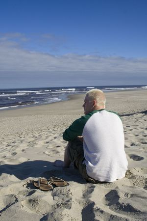 A young man quietly watches the ocean on a summer morning