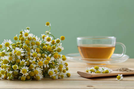 Photo pour Chamomile tea and flowers on kitchen table background - image libre de droit