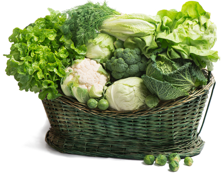 Fresh green vegetables in  wicker basket isolated on white の写真素材