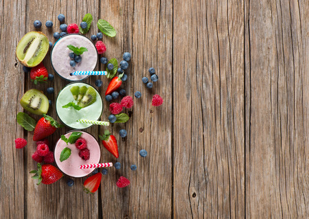 Different smoothies of berry on a wooden old background with space for text, top view