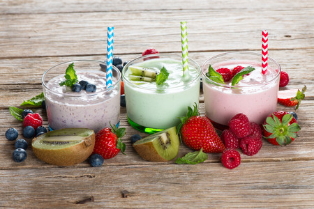 Fruit and berry healthy smoothies on a rustic wooden background