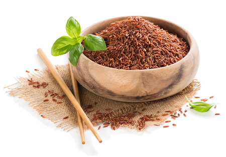 Uncooked red rice in a wooden bowl isolated on white background