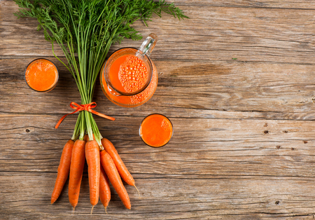 Glasses and jug of carrot juice and fresh carrots on old wooden background with space for text, top view.