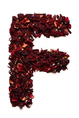 English alphabet. Letter F from dried flowers of hibiscus tea on a white background. Letters for banners, advertisements, menus.