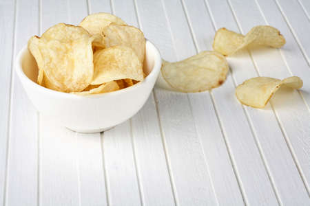 Delicious golden potato chips in a white bowl on a white wooden background. Food background.