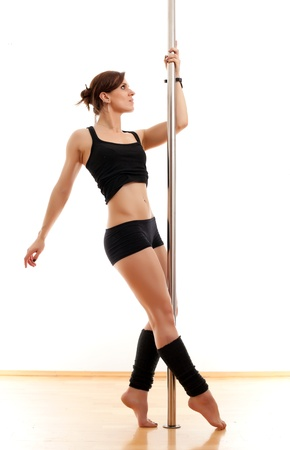 The beautiful young woman dances and keeps for a pole