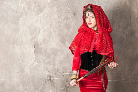 Beautiful young woman with a whip near the wall