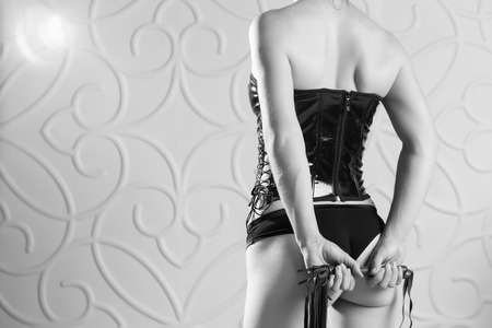 Beautiful slim woman in a black corset holds a whip