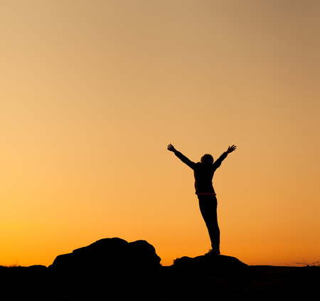 Silhouette of happy young woman with arms raised up against beautiful colorful sky. Summer Sunset. Landscape