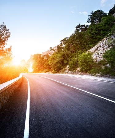 Photo pour Asphalt road in summer forest at sunset. Crimean mountains. - image libre de droit