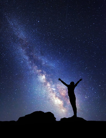 Photo for Milky Way. Night sky with stars and silhouette of a woman with raised-up arms. - Royalty Free Image