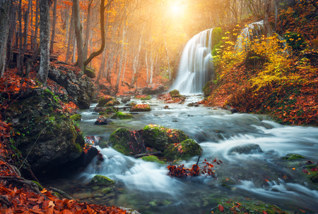 Beautiful waterfall at mountain river in colorful autumn forest with red and orange leaves at sunset. Nature landscape