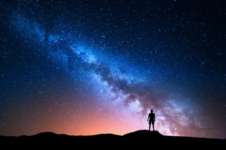 Milky Way. Beautiful night sky with stars and silhouette of a standing alone man on the mountain. Blue milky way with red light and man on the hill. Background with galaxy and silhouette of a man. Universe