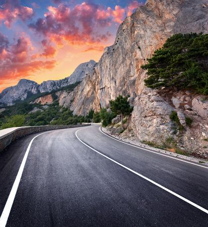Asphalt road. Colorful landscape with beautiful winding mountain road with a perfect asphalt with high rocks, amazing sky at sunset in summer. Panoramic. Travel background. Highway at mountains