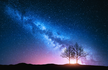 Foto de Starry sky with pink Milky Way and trees. Night landscape with alone trees on the hill against colorful milky way. Amazing galaxy. Nature background with beautiful universe. Astrophotography - Imagen libre de derechos
