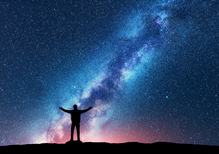 Foto de Space. Milky Way with silhouette of a standing happy man with raised up arms on the hill. Night landscape with beautiful galaxy. Universe. Night sky with stars, colorful Milky Way. Starry sky and man - Imagen libre de derechos