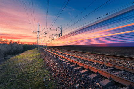 Photo pour High speed passenger train in motion on railroad at sunset. Blurred modern commuter train. Railway station and colorful sky. Railroad travel, railway tourism. Industrial landscape. Transportation - image libre de droit