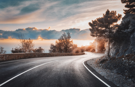 Mountain road at sunset. Landscape with rocks, sky with clouds and beautiful asphalt road in the evening in summer. Vintage toning. Travel background. Dramatic scenery with highway. Transportation
