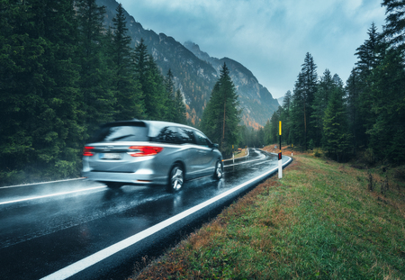 Photo pour Blurred car in motion on the road in autumn forest in rain. Perfect asphalt mountain road in overcast rainy day. Roadway, pine trees in italian alps. Transportation. Highway in foggy woodland. Travel - image libre de droit