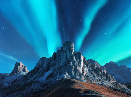 Foto per Northern lights above mountains at night in Europe. Aurora borealis. Starry sky with polar lights and high rocks. Beautiful landscape with aurora, road, buildings on the hill, mountain ridge. Travel - Immagine Royalty Free