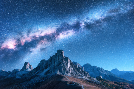 Foto de Milky Way above mountains at night in autumn. Landscape with alpine mountain valley, blue sky with milky way and stars, buildings on the hill, rocks. Aerial view. Passo Giau in Dolomites, Italy. Space - Imagen libre de derechos