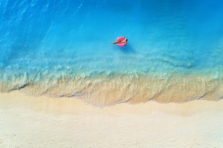 Photo pour Aerial view of a young woman swimming with the donut swim ring in the clear blue sea with waves at sunset in summer. Tropical aerial landscape with girl, azure water, sandy beach. Top view. Travel - image libre de droit