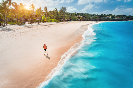 Photo pour Aerial view of the running young woman on the white sandy beach near sea with waves at sunset. Summer holiday. Top view of sporty slim girl, clear azure water. Indian Ocean. Lifestyle and sport - image libre de droit