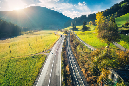 Aerial view of the road in mountain valley at sunset in spring in Dolomites, Italy. Top view of asphalt roadway, railroad, hills with green meadows, blue sky, trees, buildings. Highway and fields