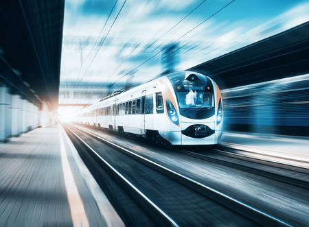 Photo pour High speed train at the railway station at sunset in Europe. Modern intercity train on railway platform. Urban scene with beautiful passenger train on railroad and buildings. Railway landscape - image libre de droit