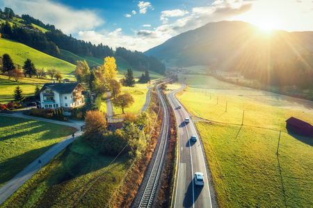 Foto de Aerial view of the road in mountain valley at sunset in spring in Dolomites, Italy. Top view of cars on asphalt roadway, house, railroad, hills with green meadows, blue sky, trees, buildings. Highway - Imagen libre de derechos