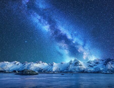 Photo for Bright Milky Way over snow covered mountains and sea at night in winter in Norway. Landscape with snowy rocks, starry sky, reflection in water, fjord. Lofoten Islands. Space. Beautiful milky way - Royalty Free Image