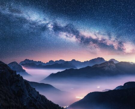 Foto de Milky Way over mountains in fog at night in summer. Landscape with foggy alpine mountain valley, purple low clouds, colorful starry sky with milky way, city illumination. Dolomites, Italy. Space - Imagen libre de derechos