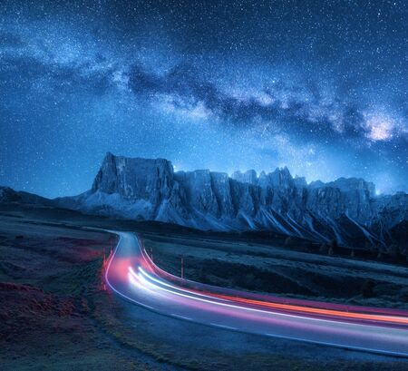 Foto de Milky Way over mountain road at night in summer. Blurred car headlights on winding road. Colorful landscape with sky with stars and blue milky way, light trails, rocks, trees and highway. Space - Imagen libre de derechos