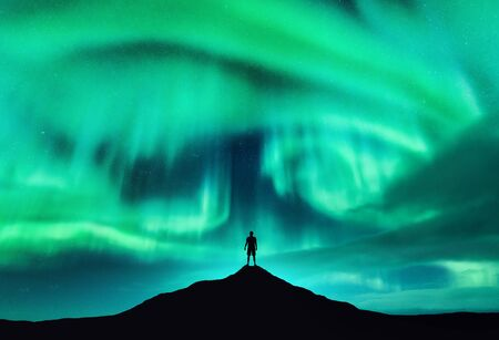 Foto de Aurora borealis and silhouette of a man on the mountain peak. Lofoten islands, Norway. Beautiful aurora and man. Alone traveler. Sky with stars and polar lights. Night landscape with northern lights - Imagen libre de derechos
