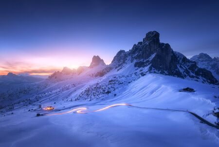 Photo pour Snowy mountains and blurred car headlights on the winding road at night in winter. Beautiful landscape with snow covered rocks, house, mountain roadway, blue starry sky at sunset in Dolomites, Italy - image libre de droit