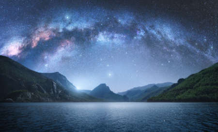 Photo for Arched Milky Way over the beautiful mountains and blue sea at night in summer. Colorful landscape with bright starry sky with Milky Way arch, moonlight, constellation, water. Galaxy. Nature and space - Royalty Free Image